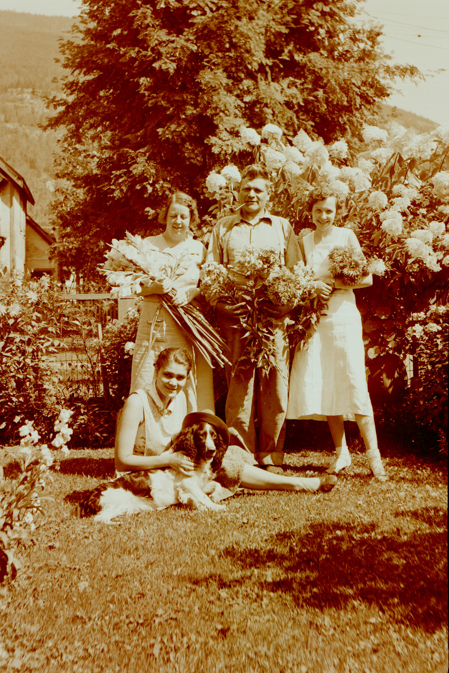 Front of house with flowers - Aida Southwell Freeman sitting and Fred Southwell, center standing